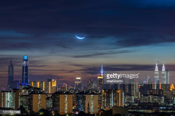 crescent moon over down town kuala lumpur - shaifulzamri stock pictures, royalty-free photos & images