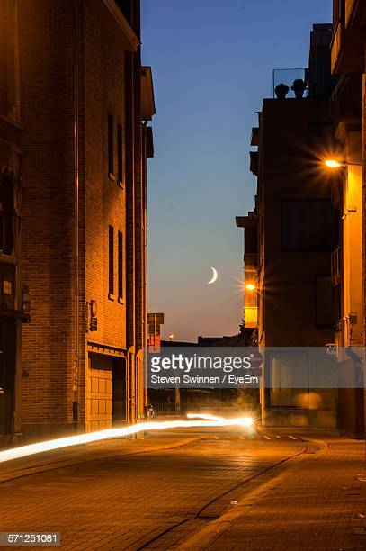 crescent moon over illuminated light trail on street in city at twilight - antwerpen stad stockfoto's en -beelden