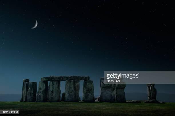 crescent moon over stonehenge monument, wiltshire, united kingdom - stonehenge stock photos and pictures