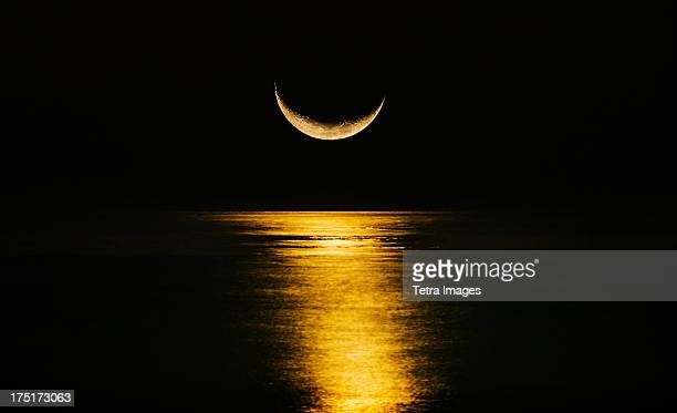 crescent moon reflecting in sea - semicírculo - fotografias e filmes do acervo