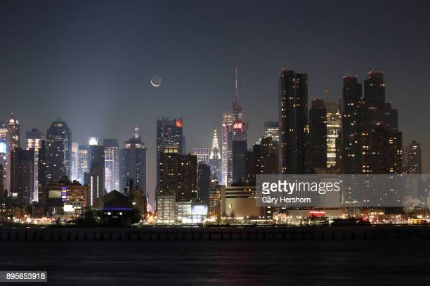 A crescent moon rises in the predawn hours over the lights of Times Square and the skyline of New York City on December 16 2017 as seen from...