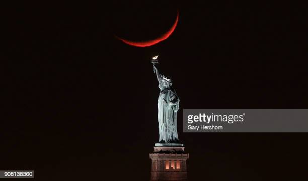 A crescent moon sets behind the Statue of Liberty on January 19 2018 in New York City