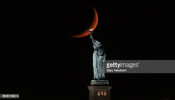 A crescent moon sets behind the Statue of Liberty on September 23 2017 in New York City