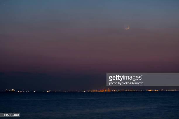 crescent moon sinking in tokyo bay - 暦月 ストックフォトと画像