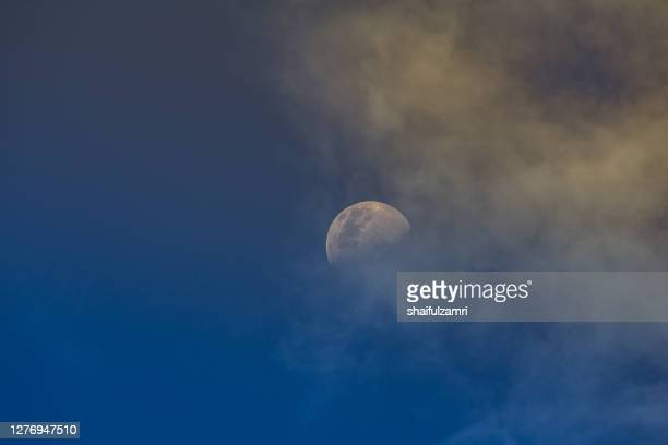 a crescent moon stands out on a blue sky at sunset. - shaifulzamri stock pictures, royalty-free photos & images
