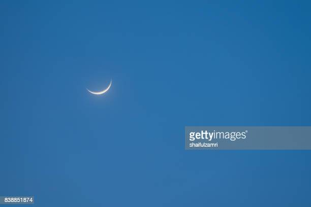 a crescent moon stands out on a blue sky at sunset - semicírculo - fotografias e filmes do acervo