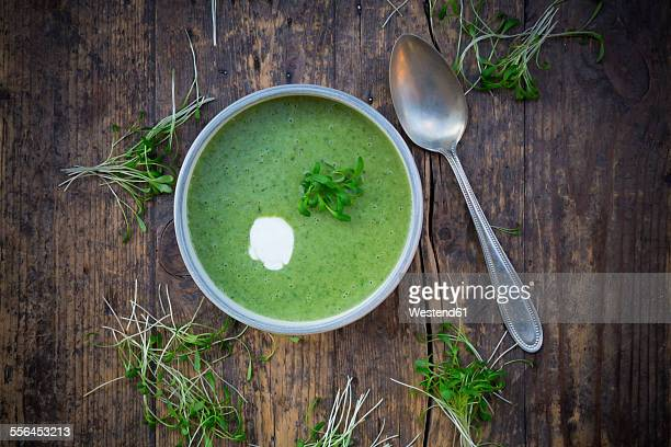 Cress soup in bowl on dark wood
