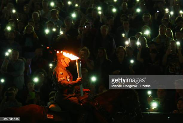 Creswick Light Horse Troop carries the torch during the 2018 AFL round five match between the Melbourne Demons and the Richmond Tigers at the...