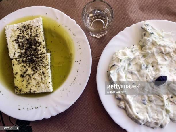 Cretan Feta Cheese with herbs and oil with a plate of Tzatziki and glass of Raki - Tsikoudia