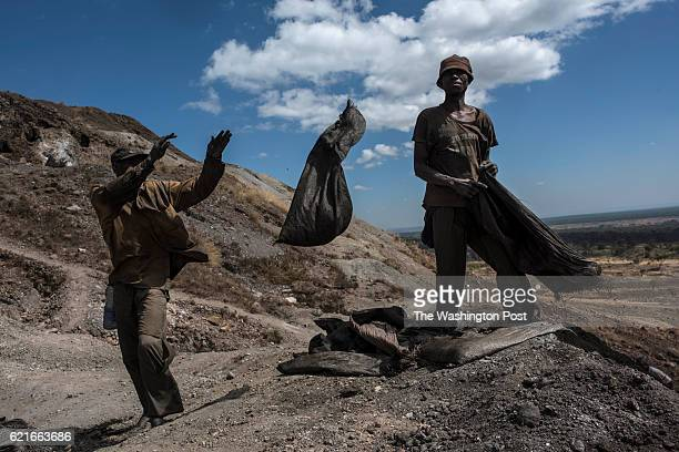 Creuseurs or diggers toss sacks of rocks at a copper and cobalt mine in Kawama Democratic Republic of Congo on June 8 2016 Cobalt is used in the...