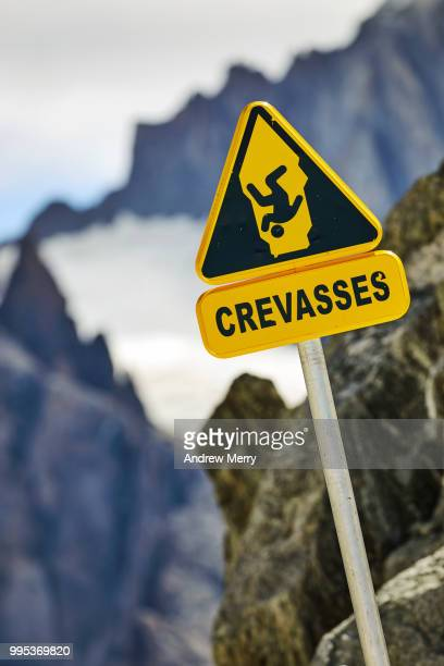 crevasses warning sign (close-up) on metal pole with a symbol of person falling into crevasse, france - pinnacle peak stock pictures, royalty-free photos & images