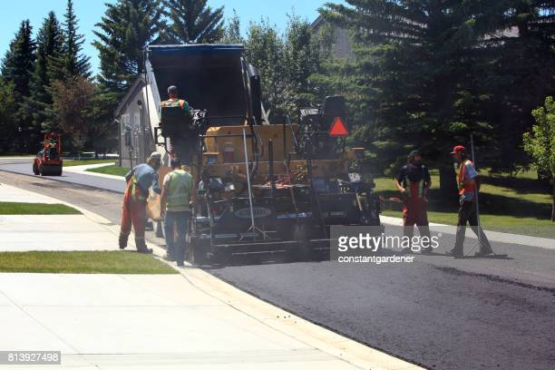 crew and equipment building totally new residential road - asphalt paving stock photos and pictures