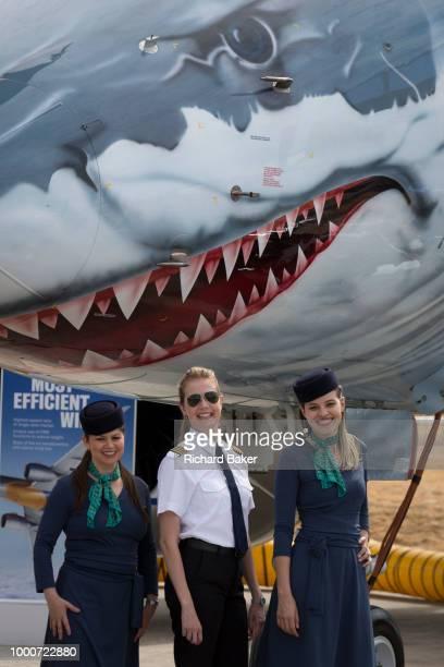 A crew beneath the shark's teeth of an Embraer E190E2 at the Farnborough Airshow on 16th July 2018 in Farnborough England