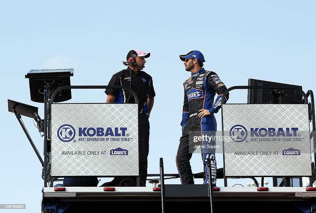 Crew chief Chad Knaus talks with Jimmie Johnson, driver of the #48 Lowe's Chevrolet, during practice for the NASCAR Sprint Cup Series Hollywood Casino 400 at Kansas Speedway on October 7, 2011 in Kansas City, Kansas.