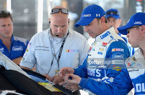 Crew chief for Jimmie Johnson driver of the Lowe's Chevrolet Chad Knaus speaks to a NASCAR official in the garage area during prerace ceremonies for...