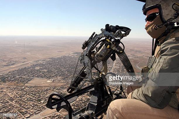 A crew chief with Marine Light Attack Helicopter Squadron 369, looks out for suspicious activity or enemy fighters while manning one of the helicopters two machine guns.