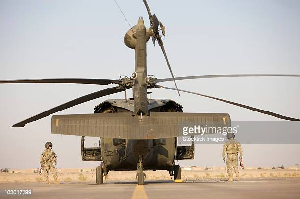 Crew Chiefs stand beside their UH-60L Black Hawk helicopter.