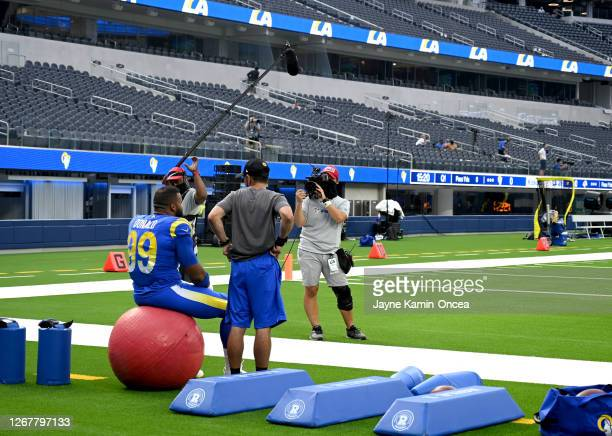 A crew from HBO's Hard Knocks films defensive tackle Aaron Donald of the Los Angeles Rams as he sits on an exercise ball looking out onto the field...