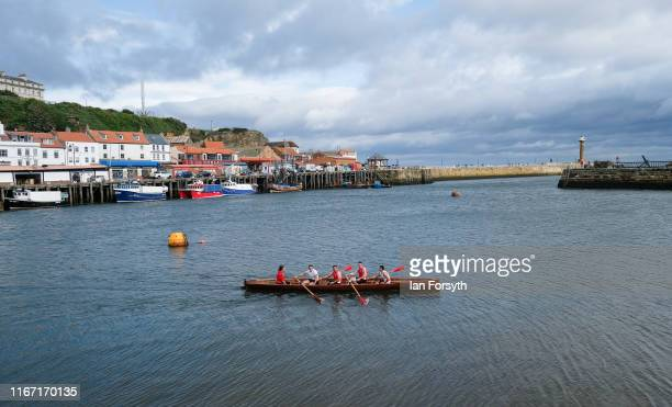 A crew from Whitby Friendship Rowing Club row across Whitby harbour as they warm up during the annual Whitby Regatta on August 10 2019 in Whitby...