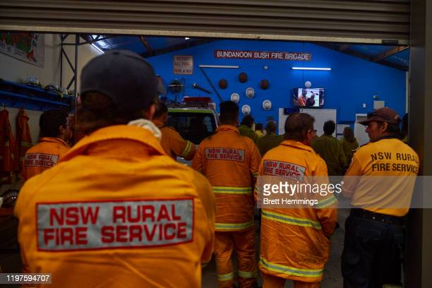 Crew gather around to watch the news on a TV in the Bundanoon RFS station on January 05, 2020 in Bundanoon, Australia. A state of emergency is in...