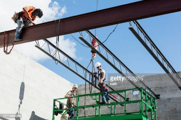 bemanning die dakbalken op bouwplaats installeert - crew stockfoto's en -beelden