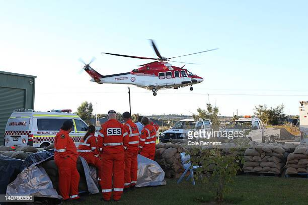 SES crew look on as the NSW Ambulance rescue helicopter takes off on March 7 2012 in Wagga Wagga Australia 9000 evacuated residents are waiting for...