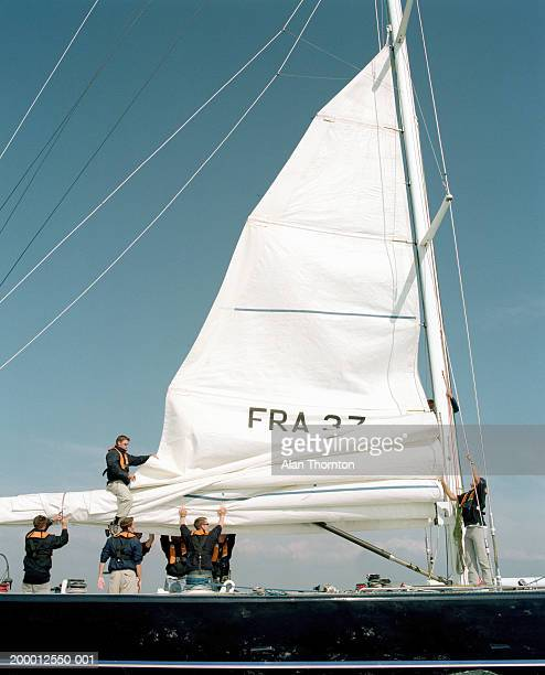 Crew lowering sail on yacht