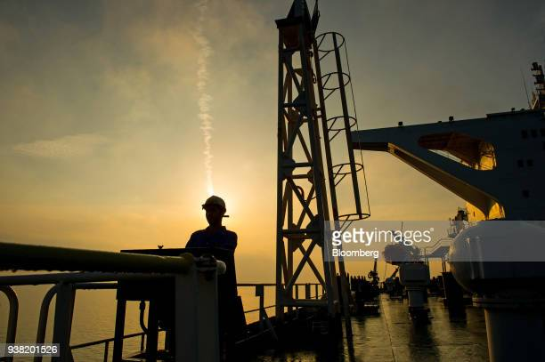 A crew man stands on the deck of the crude oil tanker 'Devon' as it sails through the Persian Gulf towards Kharq Island oil terminal to transport...