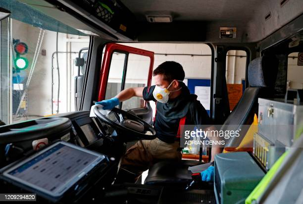 Crew Manager Lee Field uses anti-bacterial wipes to clean the steering wheel and cab of the fire engine at Station 08 following a call to a wildfire...