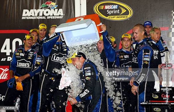Crew mebers of the Lowe's Dover White Chevrolet driven by Jimmie Johnson dump an ice cooler over crew chief Chad Knaus in victory lane after Johnson...