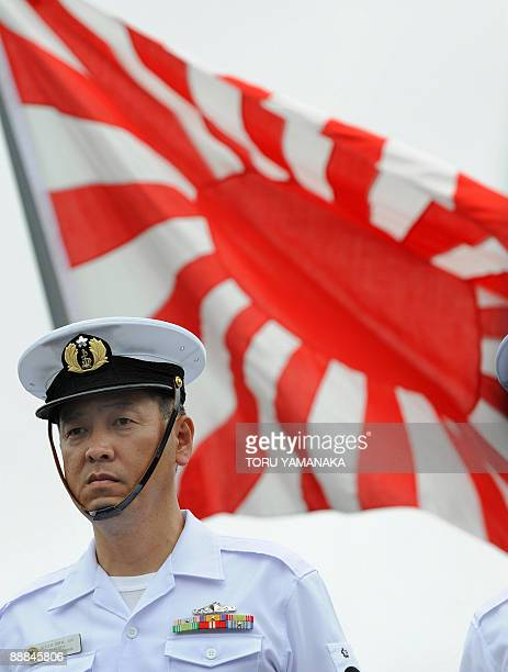 A crew member aboard Japan's Maritime SelfDefence Force destroyer Harusame stands in front of a navy flag as it sets sail for an antipiracy mission...