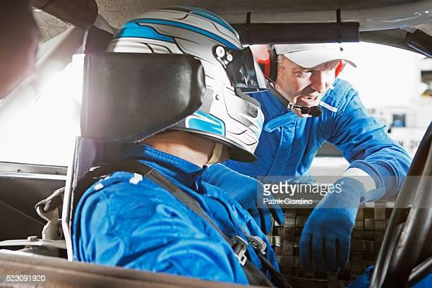 Crew member and stock car driver communicating