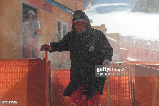 A crew member braves strong winds after the Women's Giant Slalom was cancelled at the Jeongseon Alpine Center during the Pyeongchang 2018 Winter...