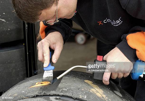 A crew member burns away worn rubber on a tire during practice Saturday October 18 2003 at the NASCAR Subway 500 at Martinsville Speedway...