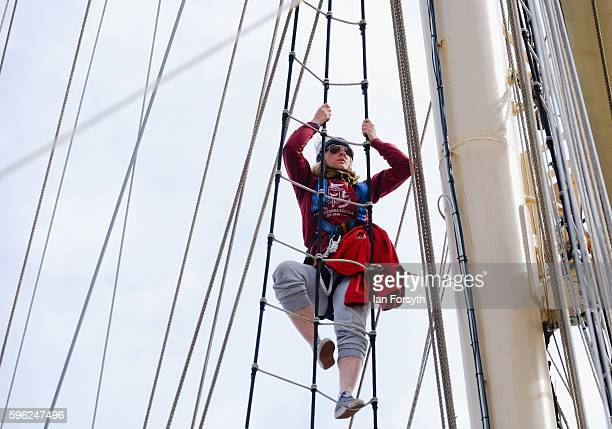 A crew member climbs up into the rigging during the North Sea Tall Ships Regatta on August 27 2016 in Blyth England The bustling port town in South...