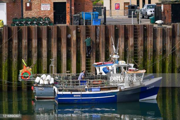 A crew member climbs up to the quayside from a fishing boat moored in the harbour in Scarborough UK on Tuesday June 2 2020 The threat of a nodeal...