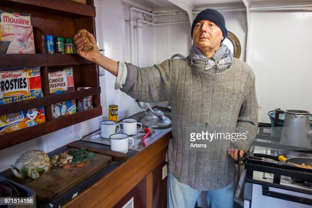 Crew member cooking breakfast in galley of the last Iceland trawler Amandine renovated fishing boat now museum in Ostend Belgium