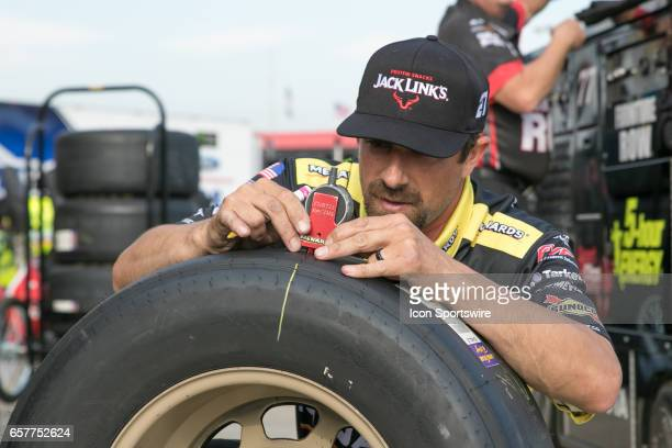 A crew member for the Paul Menard Richard Childress Racing Team checks the balance of tires after the conclusion of qualifying for the Auto Club 400...