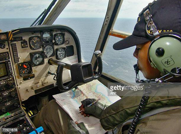 A crew member from an Indonesian Navy surveillance plane checks his map during a search mission after leaving Makassar for the missing Adam Air...