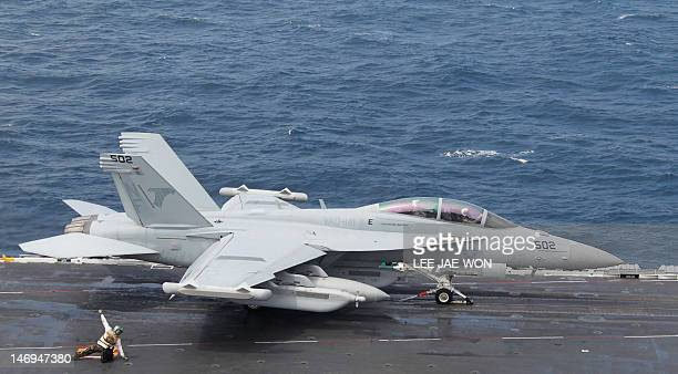 A crew member guides a US Navy F/A18 Super Hornet fighter as it takes off from the deck of the US aircraft carrier USS George Washington during joint...