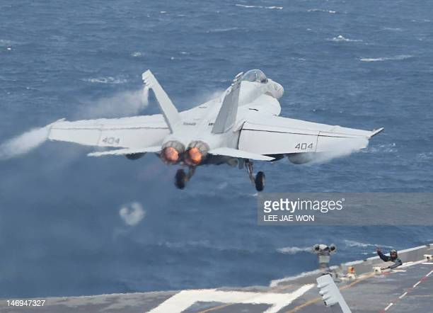 A crew member guides a US Navy F/A18 Super Hornet fighter taking off from the deck of the US aircraft carrier USS George Washington during joint...