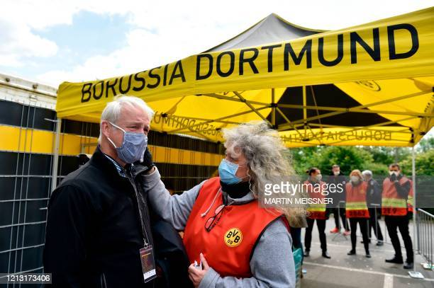 Crew member has his temperature checked before entering the stadium for the German first division Bundesliga football match BVB Borussia Dortmund v...