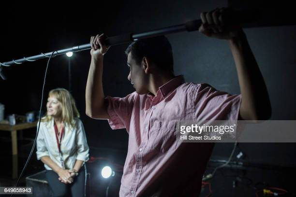 Crew member holding boom microphone on set