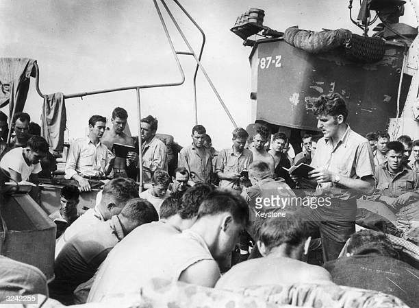 A crew member leads his shipmates in hymn singing and prayer aboard an American Navy LST ship on its way to Iwo Jima