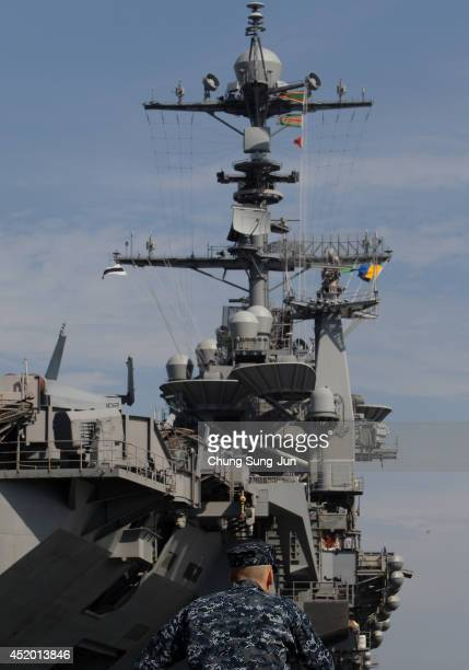 Crew member looks Aircraft Carrier USS George Washington whilst at anchor in Busan port on July 11 2014 in Busan South Korea The US Navy's aircraft...