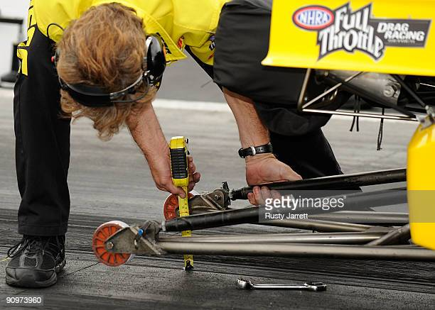A crew member makes adjustments to the wheelie bar during qualifying for the NHRA Carolinas Nationals on September 19 2009 at Zmax Dragway in Concord...