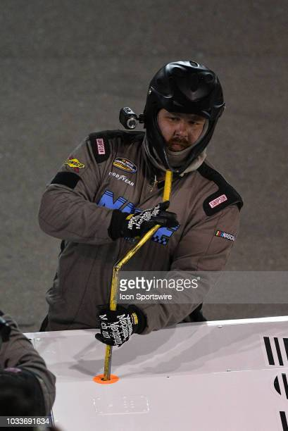 A crew member makes an adjustment on the truck of Justin Fontaine ProMATIC Automation Superior Essex Chevrolet Silverado during the NASCAR Camping...