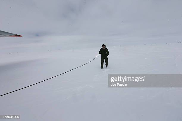A crew member of a skiequipped C130 from the New York Air National Guard stands near the plane at Summit Station which is a scientific research...