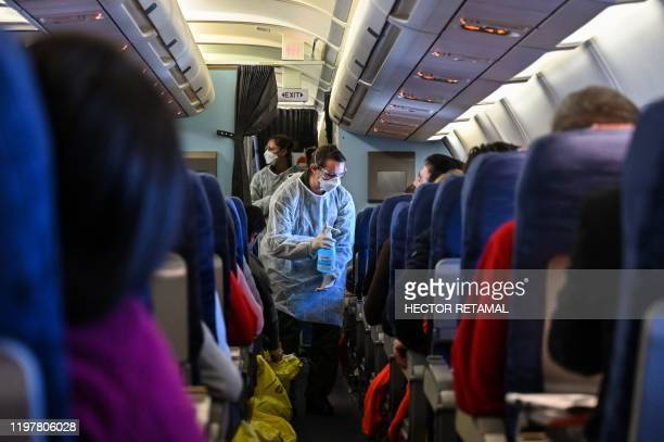 A crew member of an evacuation flight of French citizens from Wuhan gives passengers disinfectant during the flight to France on February 1 as they...