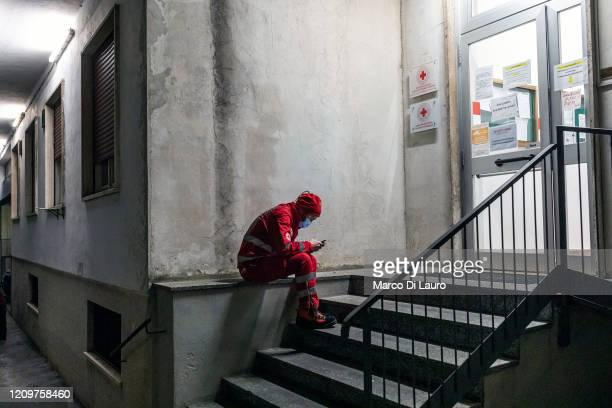 A crew member of an Italian Red Cross ambulance sits on the steps of the headquarters during his shift while waiting for emergency calls on April 4...